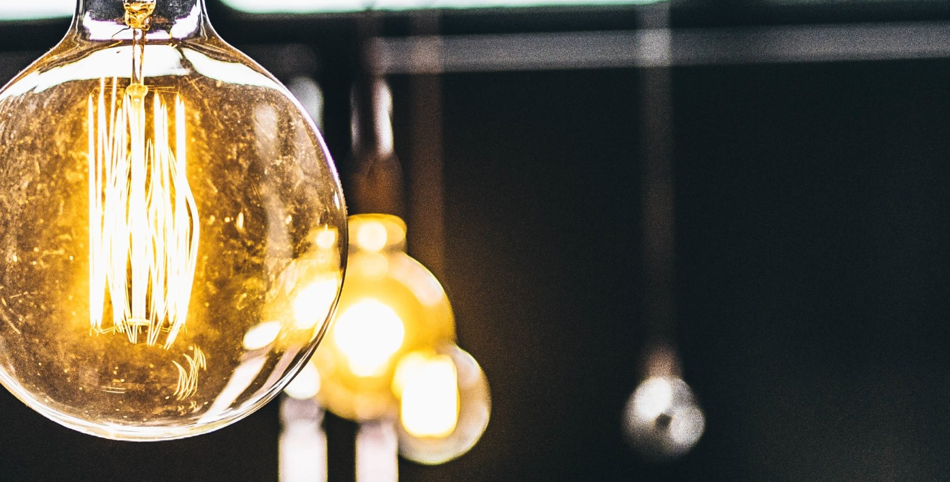 Several large round filament lightbulbs just out of focus